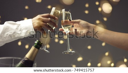 Close up of dark skinned man and caucasian woman toasting with glasses of sparkling wine on gray background with lights and lens flare #749415757