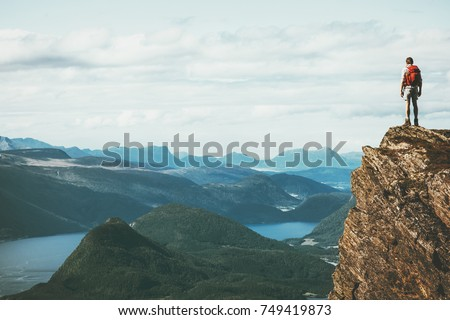 Life on the edge Traveler on cliff mountains over fjord enjoying Norway landscape Travel Lifestyle success motivation concept adventure active vacations outdoor Royalty-Free Stock Photo #749419873