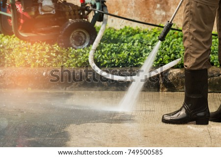 Worker cleaning driveway with gasoline high pressure washer splashing the dirt,professional cleaning services.High pressure cleaning,lower body. #749500585