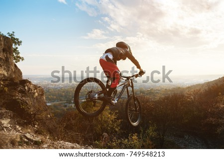 a young rider at the wheel of his mountain bike makes a trick in jumping on the springboard of the downhill mountain path in the autumn forest #749548213