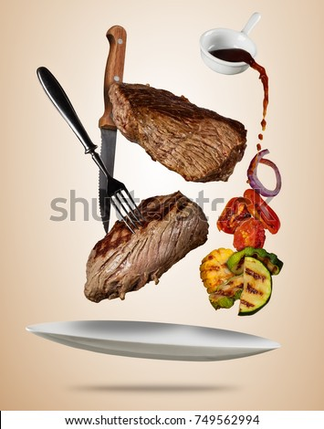 Flying beef steaks with grilled vegetable served on plate. Concept of flying food. Separated on soft colored background. High resolution size