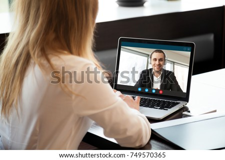 Businesswoman making video call to business partner using laptop. Close-up rear view of young woman having discussion with corporate client. Remote job interview, consultation, human resources concept #749570365