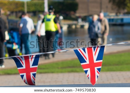 Union jack flag bunting with policeman in the background in hi vis vest