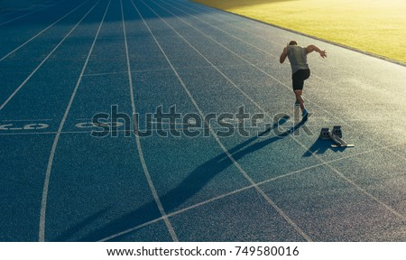 Athlete running on an all-weather running track alone. Runner sprinting on a blue rubberized running track starting off using a starting block. Royalty-Free Stock Photo #749580016
