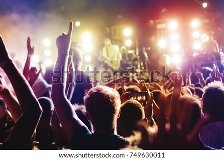 Concert Crowd. Silhouettes young people in front of bright stage lights. Band of rock stars #749630011
