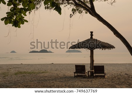 Lounge chairs and a sunshade umbrella on the tropical beach #749637769