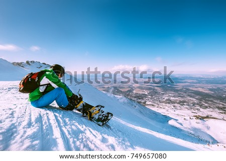 Snowboarder fastens snowboard buckles sitting on the top of snow hill #749657080