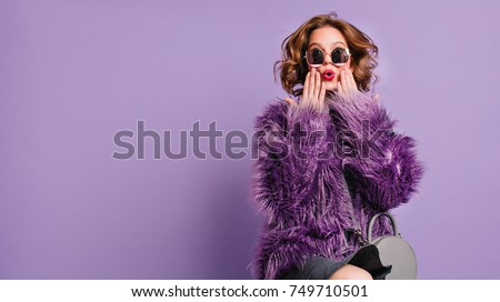 Spectacular young woman with trendy makeup posing with surprised face expression on bright purple background. Indoor photo of shocked female model in stylish fur jacket.
