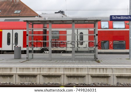 trainstation with train passing by and rails with infrastructure beside in south germany city near munich and stuttgart #749826031