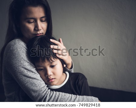 Sad little boy being hugged by his mother at home. Parenthood, Love and togetherness concept. #749829418