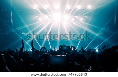 Happy people dance in nightclub party concert and listen to the music from DJ on the stage in the background. #749905843