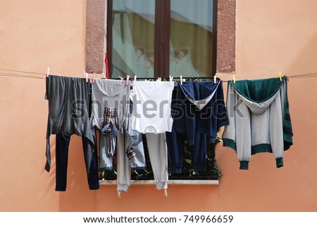 Line of hanging clothes in front of window on a pastel colored wall in Lisbon, Portugal #749966659