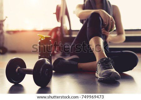 Woman exercise workout in gym fitness breaking relax holding apple fruit after training sport with dumbbell and protein shake bottle healthy lifestyle bodybuilding, Athlete builder muscles lifestyle. #749969473