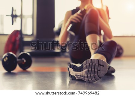 Woman exercise workout in gym fitness breaking relax holding protein shake bottle after training sport with dumbbell and healthy lifestyle bodybuilding, Athlete builder muscles lifestyle. #749969482