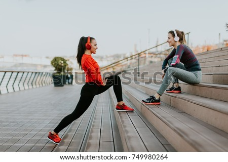Young woman exercising with a personal trainer outside in the morning #749980264