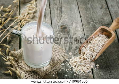 Pouring oat milk on rustic wood background, copy space #749984305