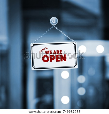 WE ARE OPEN sign board through the glass of store window. Filtered image. #749989255
