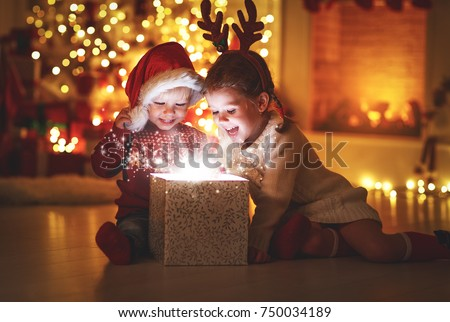 Merry Christmas!happy children with magic gift at home near  Christmas tree and fireplace