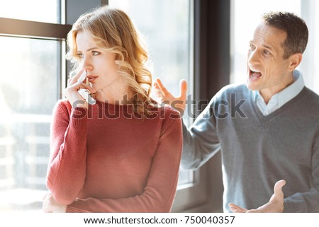 Conflict in the family. Angry emotional man standing behind his wife and shouting at her while expressing his emotions #750040357