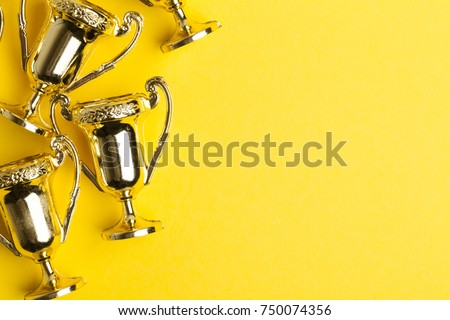 Gold winners achievement trophy on a yellow background Royalty-Free Stock Photo #750074356