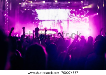 Cheering crowd with hands in air at music festival #750076567