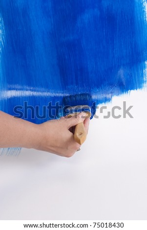 painting a wall with paint brush in blue #75018430