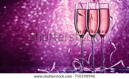 Picture of three wine glasses with sparkling champagne with white ribbons on pink background