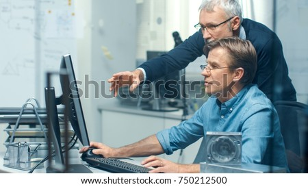 In Busy Engineering Bureau Two Senior Engineers Discussing Technical Issues over Personal Computer. Their Office Looks Minimalistic and Modern. #750212500
