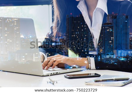 Double exposure of city and woman hand keyboard.  Business girl using laptop computer sitting working office. Attractive Female Assistant Working Typing Using Portable Computer for finance and busing #750223729