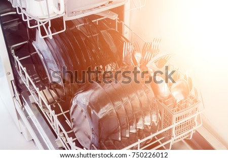 An open dishwasher with clean dishes in a white kitchen, front view. utensils, selective focus. Dishwasher with clean white dishes #750226012