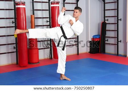 Young man practicing karate in dojo #750250807