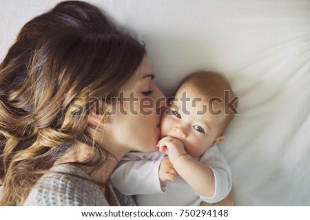 A Mother and baby child on a white bed. #750294148
