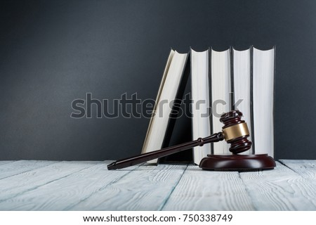 Law concept - Open law book with a wooden judges gavel on table in a courtroom or law enforcement office on blue background. Copy space for text #750338749