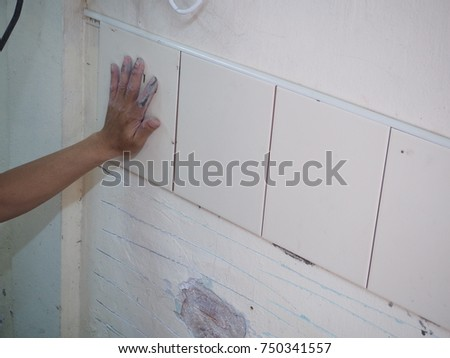 Hand professional construction worker the process of tiling is in the wall. #750341557