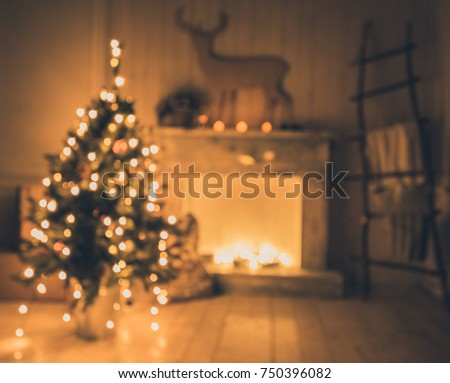 Defocused interior with christmas tree with bokeh lights and a fireplace