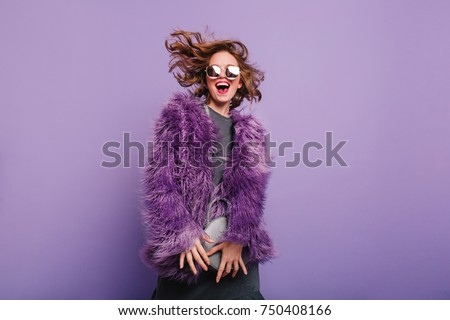 Gorgeous short-haired girl in sunglasses dancing on purple background with happy smile. Laughing female model in elegant fur coat posing in studio with little handbag. #750408166