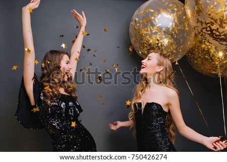 Inspired curly pale woman singing with hands up on dark background. Romantic blonde girl in black outfit holding party balloons and looking at friend which dancing under confetti. Royalty-Free Stock Photo #750426274