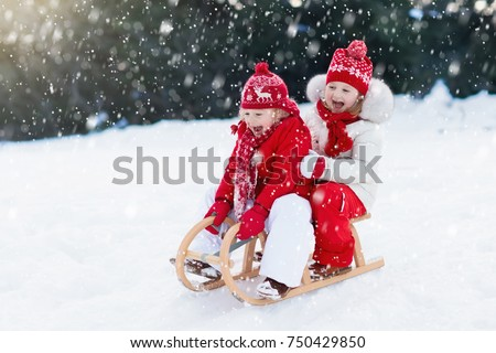 Little girl and boy enjoy a sleigh ride. Child sledding. Toddler kid riding a sledge. Children play outdoors in snow. Kids sled in Alps mountains in winter. Outdoor fun for family Christmas vacation. #750429850