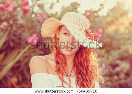 Woman in straw hat with white teeth thinking and looking sideways in a park in summer, flower shrub bush on background #750435910