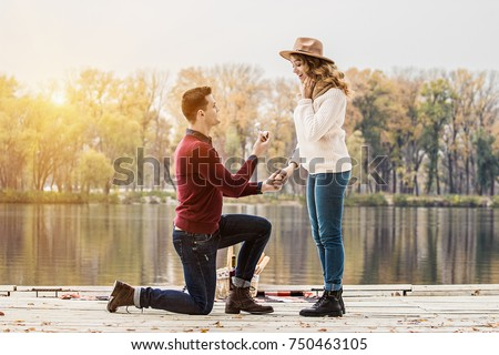 Marry me. Horizontal shot of young man in casual clothing standing on one knee and holding engagement ring while making wedding proposal to his beautiful girlfriend. Engagement of young couple. #750463105