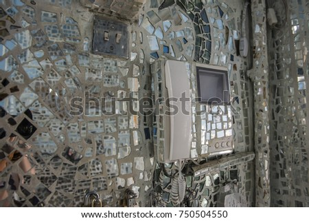 Photo of the interior of a house covered with mirror mosaic, the wall and the phone is covered with small mirror pieces. Captured in Kuwait.  #750504550