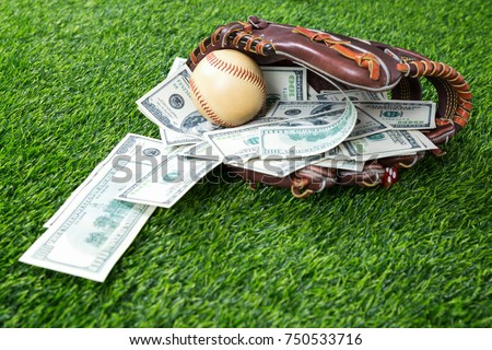 Close up of  baseball in a Glove with dollar bills in concept of getting money with bets in baseball #750533716