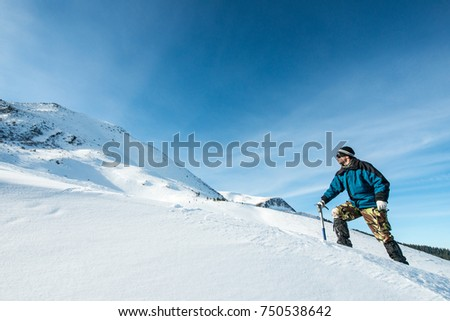 climber with an ice ax in the snowy mountains #750538642