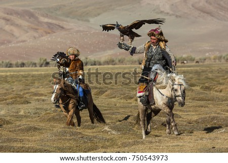 SAGSAY, MONGOLIA - SEP 28, 2017: Kazakh Eagle Hunters traditional clothing, while hunting to the hare holding a golden eagles on his arms in desert mountain of Western Mongolia. #750543973