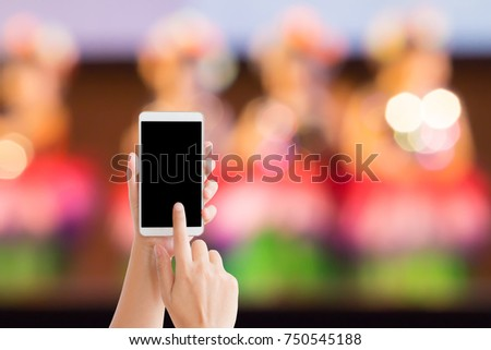 woman use mobile phone and blurred image of the children dance show on the stage #750545188