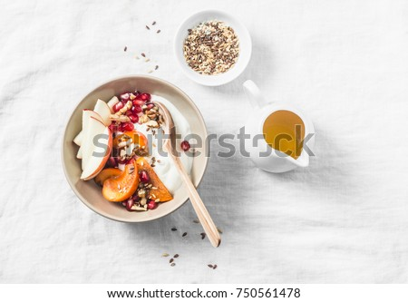 Full fruit and greek yogurt breakfast bowl. Persimmon, apple, walnuts, pomegranates and natural yogurt. Healthy food concept on light background, top view      #750561478