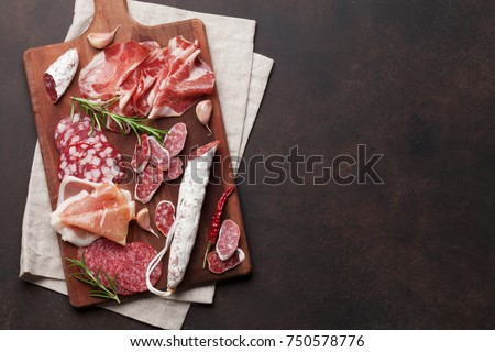 Salami, sliced ham, sausage, prosciutto, bacon. Meat antipasto platter on stone table. Top view with copy space #750578776