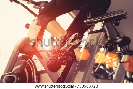 Exercise bike cardio workout at fitness gym of woman taking weight loss with machine aerobic for slim and firm healthy in the morning, Athlete builder muscles lifestyle. #750583723