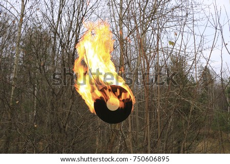 The old vinyl black record is embraced by a bright strong flame #750606895
