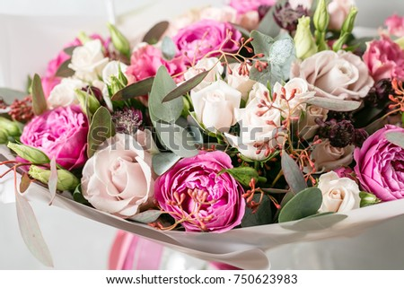 beautiful bouquet of mixed flowers into a vase on wooden table #750623983